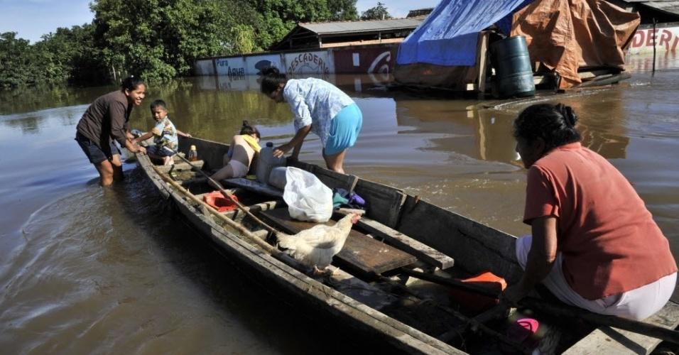 18.fev.2014 - Família tenta recuperar pertences em área alagada pelo rio Mamoré em Trinidad, na Bolívia, nesta segunda-feira (17). O governo boliviano declarou estado de emergência devido às chuvas no país, que já causaram a morte de 56 pessoas e afetaram mais de 58 mil casas