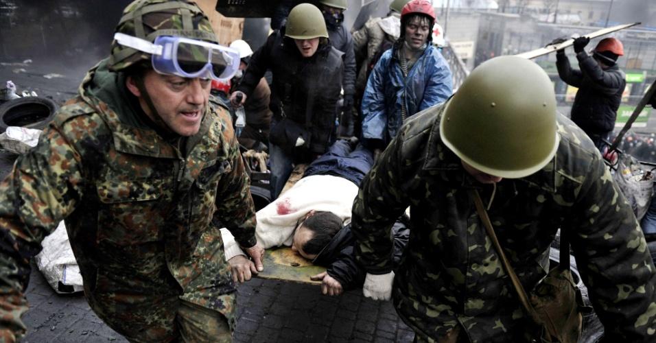 20.fev.2014 - Manifestantes carregam colega ferido durante confrontos com a polícia na praça da Independência, em Kiev (Ucrânia), nesta quinta-feira (20). Centenas de manifestantes armados montaram atacaram barricadas da polícia, apesar de uma trégua acordada apenas algumas horas antes pelo presidente do país. Os manifestantes empurraram a polícia de volta cerca de 200 metros, tomando controle da maior parte da praça, terreno perdido na última ação policial, realizada na terça-feira