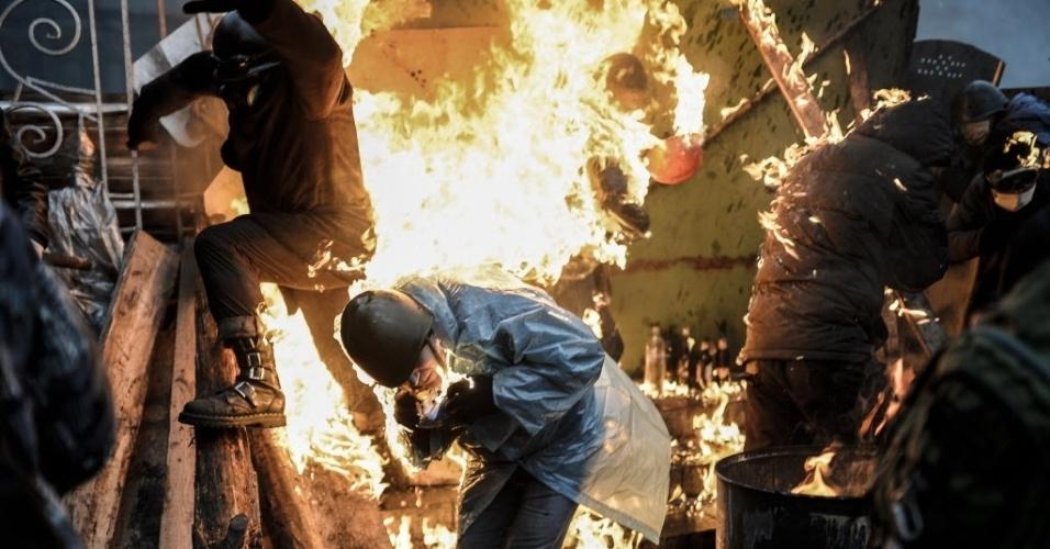 20.fev.2014 - Manifestantes são atingidos por chamas atrás de barricadas durante confronto com a polícia na praça da Independência, em Kiev