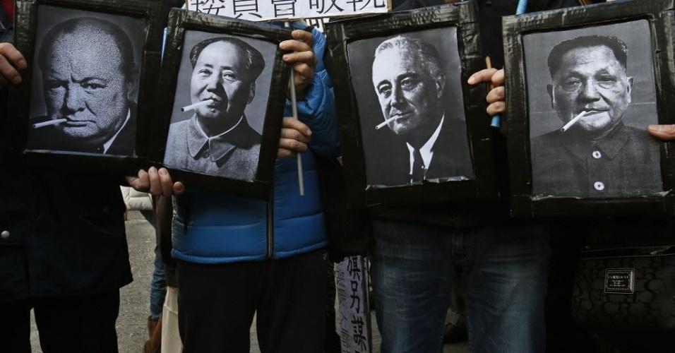 20.fev.2014 - Manifestantes seguram fotografias que mostram montagens de figuras políticas conhecidas por serem fumantes durante um protesto contra o aumento de impostos sobre os cigarros, em Hong Kong, China