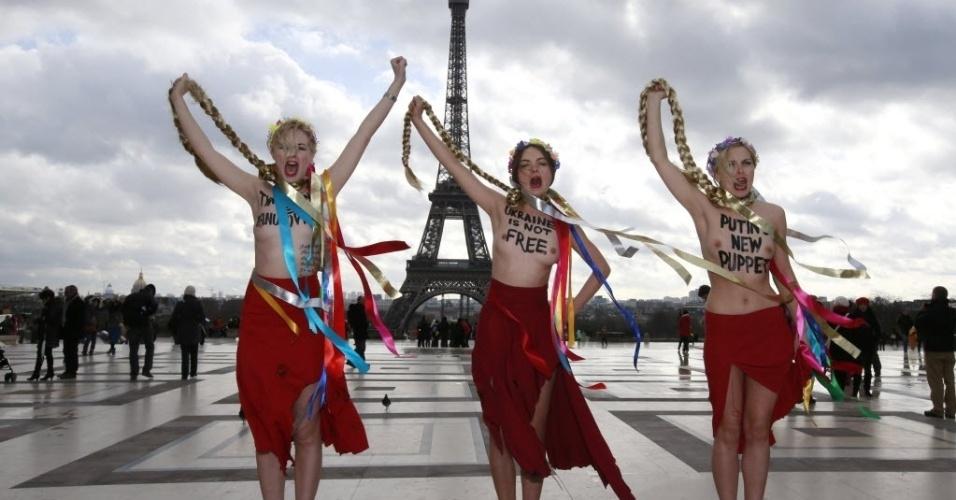 25.fev.2014 - Ativistas do grupo Femen simulam enforcamento com tranças semelhantes as da ex-primeira-ministra ucraniana Yulia Timoshenko, perto da torre Eiffel, em Paris. O Femen classificou a líder da oposição como