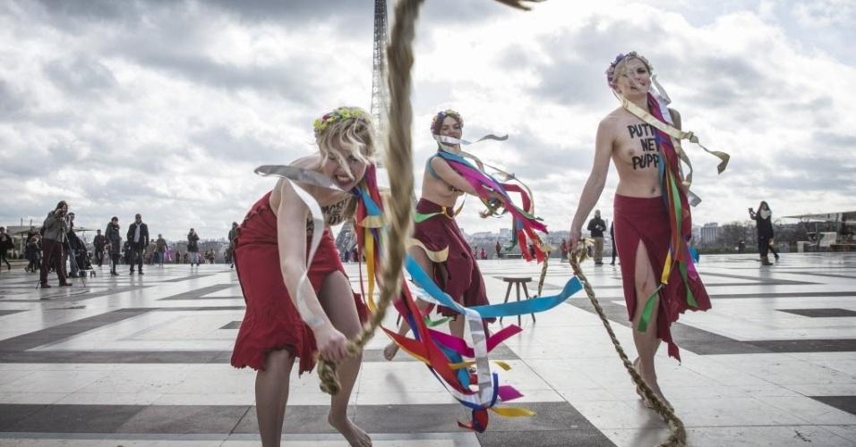 25.fev.2014 - Ativistas do grupo Femen usam tranças semelhantes as da ex-primeira ministra ucraniana Yulia Timoshenko, perto da Torre Eiffel, em Paris. O Femen classificou a líder da oposição como