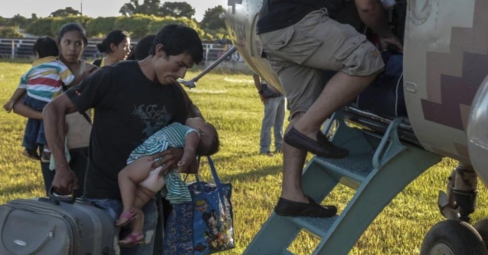 26.fev.2014 - Com a ajuda de um helicóptero militar peruano, pessoas são retiradas de Santa Ana de Yacuma, cidade da região boliviana de Beni afetada por enchentes. As fortes chuvas na região causaram enchentes em todo o nordeste da Bolívia
