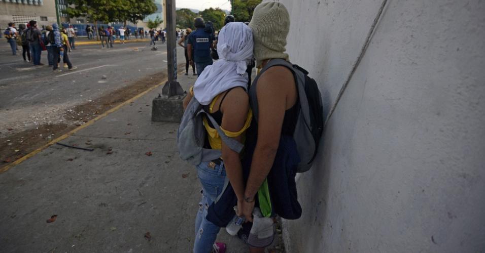 28.fev.2014 - Casal de manifestantes se abraça durante protesto contra o governo de Nicolás Maduro, em Caracas, na Venezuela, nesta sexta-feira (28). Eles denunciam violações de direitos humanos no país
