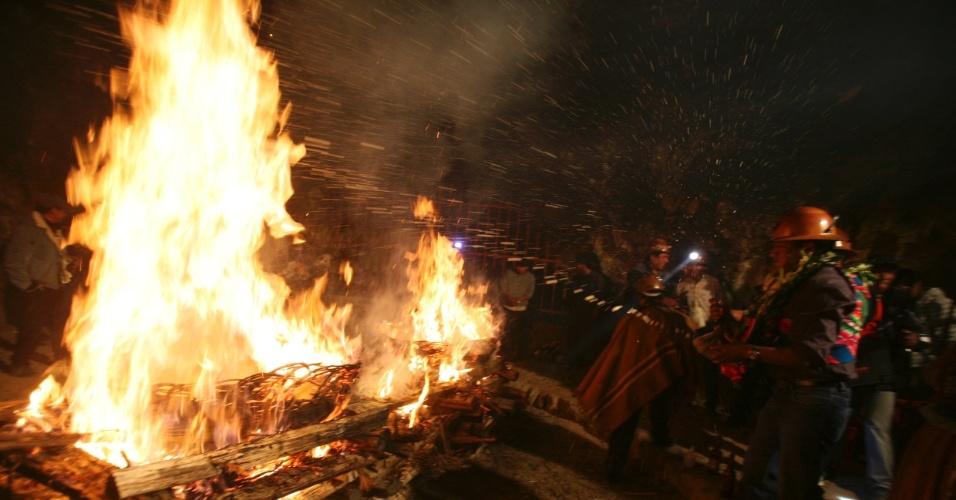 28.fev.2014 - Mineiros jogam cerveja em uma fogueira como oferenda em um ritual de celebrarção na mina Itos, na Bolívia, nesta sexta-feira (28). Trabalhadores abençoam a mina através de um sacrifício de um animal, durante o Carnaval andino