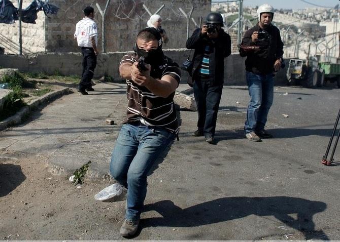 28.fev.2014 - Oficial da polícia israelense aponta arma para fotógrafos em Jerusalém, durante confronto entre palestinos e forças segurança de Israel