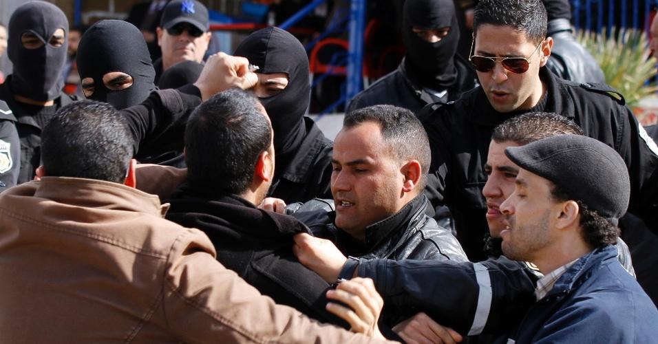28.fev.2014 - Policiais detêm um apoiador da (LPR) Liga Nacional para a Proteção da Revolução durante protesto pela libertação do líder da LPR Imed Dghij, na praça Kasbah, onde está situada a sede do governo em Túnis, na Tunísia, nesta sexta-feira (28). Dghij foi preso esta semana por insultar a polícia através da internet, de acordo com agências locais de notícias