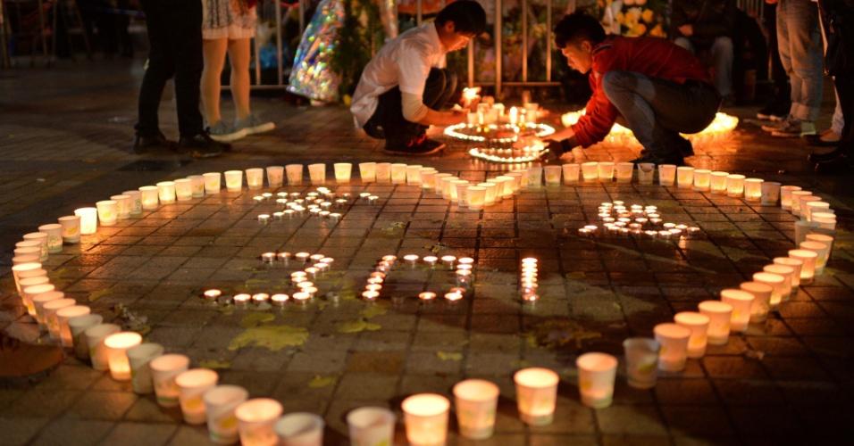 2.mar.2014 - Chineses acendem velas na principal estação de trem de Kunming, província de Yunnan, sudoeste da China, no domingo (2), em homenagem aos 33 mortos durante ataque terrorista no local no sábado (1º). A China acusou militantes separatistas de Xinjiang ? região muçulmana no extremo oeste - de envolvimento no atentado