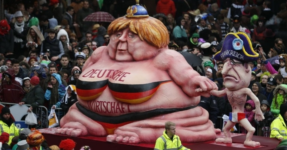 3.mar.2014 - Carro alegórico com caricatura da chanceler alemã Angela Merkel e do presidente francês François Hollande desfila em parada de Carnaval de Dusseldorf, na Alemanha