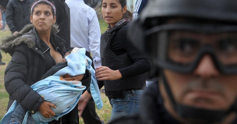 3.mar.2014 - Mulher amamenta seu filho enquanto manifestantes entram em confronto com a polícia durante um despejo de pessoas que ocuparam um imóvel no bairro de Villa Lugano, na cidade de Buenos Aires, na Argentina, nesta segunda-feira