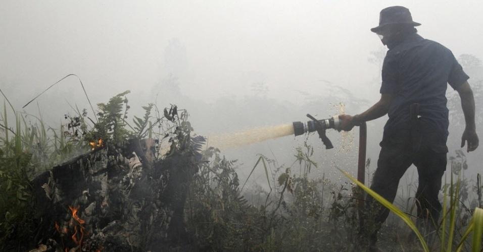 3.mar.2014 - Nesta fotografia tirada no dia 1º de março e divulgada nesta segunda-feira (3), um bombeiro da Indonésia apaga incêndio ardente em turfeiras na província de Riau, em Sumatra, uma ilha da Indonésia