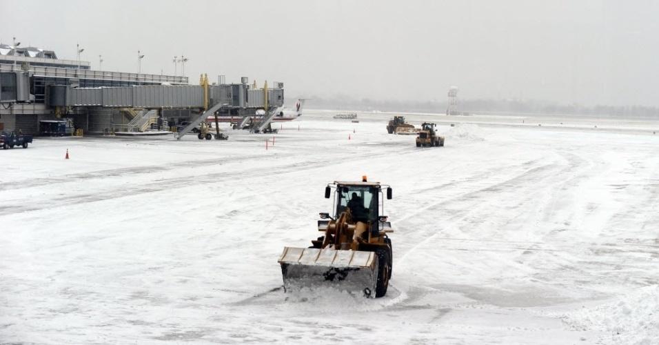 3.mar.2014 - Os trabalhadores limpar uma pista no Aeroporto Nacional Reagan durante uma tempestade de neve em Washington, nos Estados Unidos, nesta segunda-feira (3)