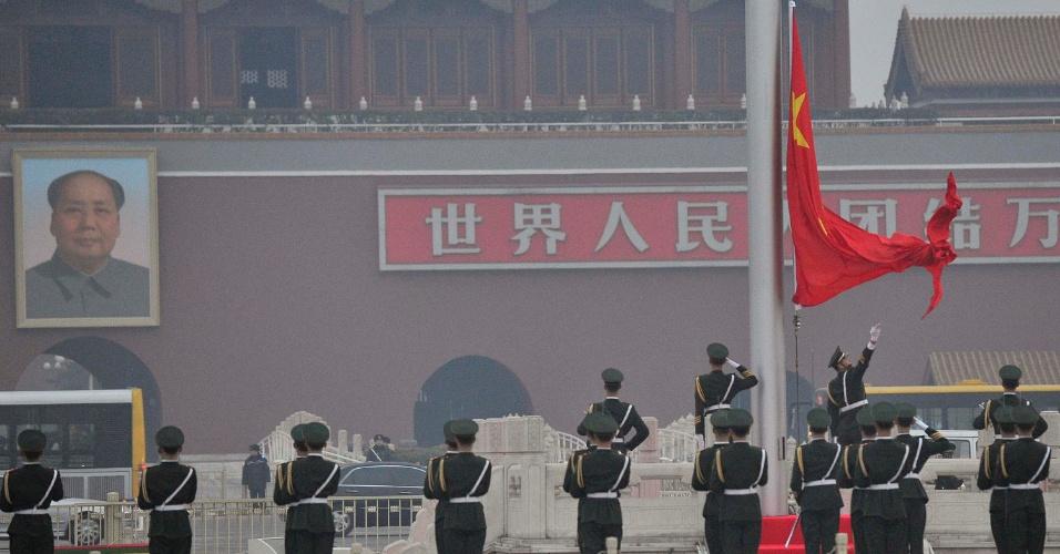 3.mar.2014 - Policial hasteia bandeira da China em frente ao retrato do falecido presidente Mao Zedong antes da abertura da Conferência Consultiva Política do Povo Chinês (CCPPC) na praça Tiananmen, em Pequim, nesta segunda-feira (3)