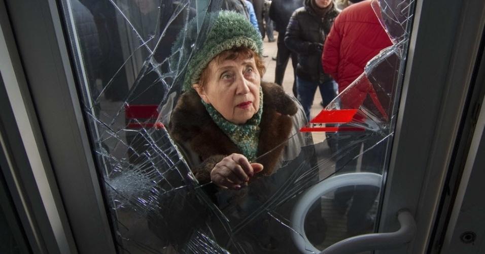 3.mar.2014 - Uma mulher olha através da porta de entrada do prédio do governo regional em Donetsk, na Ucrânia, nesta segunda-feira (3). Manifestantes pró-russos ocuparam o primeiro andar do prédio do governo nesta segunda-feira e colocaram no edifício de 11 andares bandeiras russas, ao invés da bandeiras ucranianas