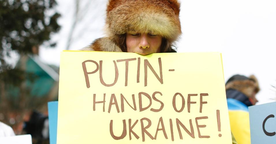 4.mar.2014 - Uma manifestante segura um cartaz com a boca enquanto participa de um protesto contra as tropas russas na Ucrânia, fora da embaixada russa em Ottawa, no Canadá, nesta terça-feira (4)