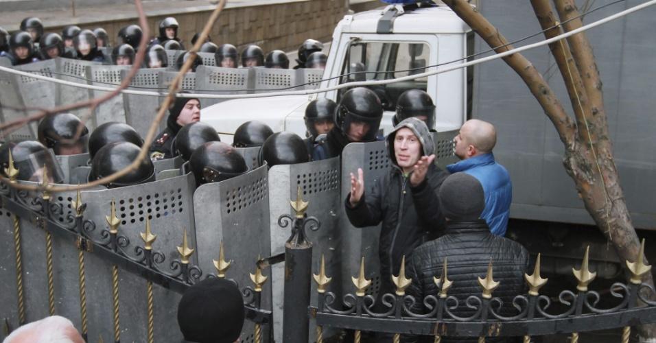 5.mar.2014 - Manifestantes enfrentam a tropa de choque em frente à sede da delegação do governo central ucraniano em Donetsk, no leste da Ucrânia, nesta quarta-feira (5). A polícia acabou com a manifestação pró-russos sob o pretexto de uma ameaça de bomba no prédio