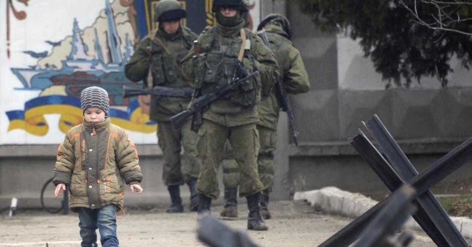 5.mar.2014 - Menino caminha em frente a militares russos que bloqueiam o acesso da Marinha ucraniana. Forças russas assumiram o controle parcial de uma base de lançamento de mísseis em Evpatoria, oeste da Crimeia região autônoma da Ucrânia cuja maioria é alinhada à Rússia