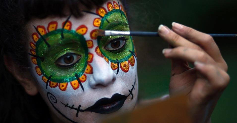 """5.mar.2014 - Uma participante do grupo de teatro de rua """"Murga Cachengue y Sudor"""" faz retoques em sua maquiagem para ir para uma praça pública antes do desfile de Carnaval, em Buenos Aires, na Argentina, na última terça-feira (4). A foto foi divulgada nesta quarta-feira (5)"""