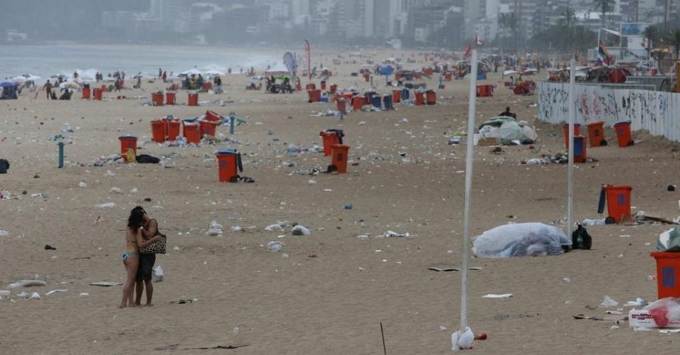 6.mar.2014 - Casal se beija na areia da praia de Ipanema, na zona sul do Rio de Janeiro, em meio a lixeiras que transbordam cheias de dejetos, nesta quinta-feira (6). Em greve desde o último sábado (1º), cerca de 500 garis decidiram, em assembleiana frente da Comlurb (Companhia Municipal de Limpeza Urbana), manter a paralisação