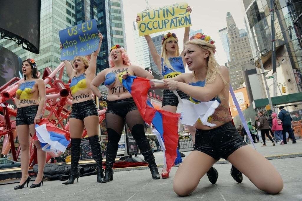 6.mar.2014 - Líder do grupo feminista Femen, Inna Shevchenko (direita), rasga uma bandeira russa enquanto protesta ao lado de outras ativistas, contra a intervenção russa na Ucrânia e em apoio a sanções impostas pelos Estados Unidos , na Times Square, em Nova York