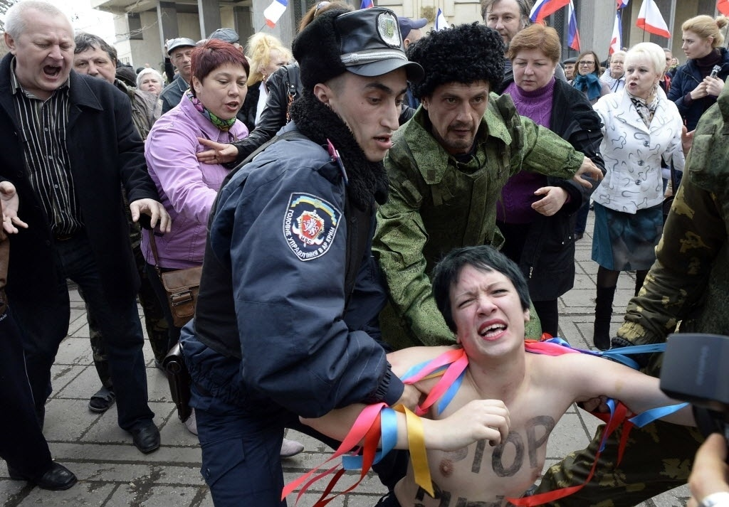 6.mar.2014 - Oficial da policia ucraniana e voluntário pró-Rússia seguram uma ativista do Femen que protestava contra a guerra em frente ao Parlamento da Crimeia, durante um comício de apoio a Rússia