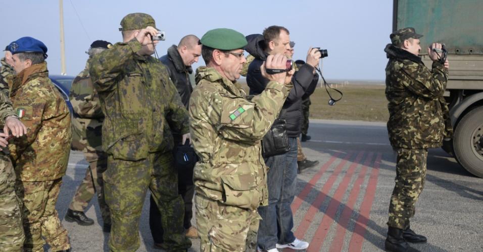 7.mar.2014 - Militares da OSCE tiram fotos durante as negociações com as forças pró-russas que estão bloqueando a entrada para Crimeia no ponto de verificação Chongar, nesta sexta-feira (7). Dois ônibus que transportavam observadores da OSCE voltaram a tentar entrar na Crimeia depois de terem sido parados por homens armados em um posto de controle
