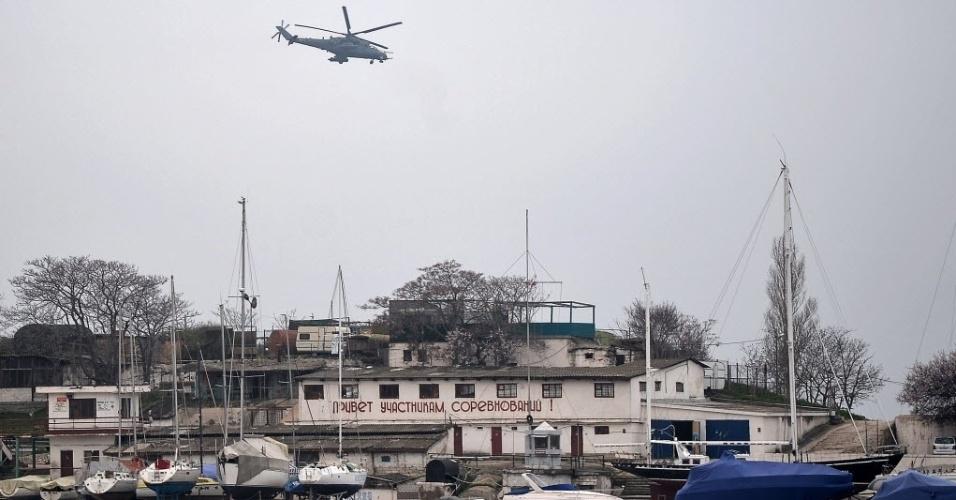 7.mar.2014 - Um helicóptero militar russo MI24 voa sobre o porto de Sebastopol, na Ucrânia, nesta sexta-feira (7). Observadores militares da OSCE, que foram impedidos de entrar Crimeia ontem vão fazer novas tentativas para entrar na península do mar Negro, nesta sexta-feira