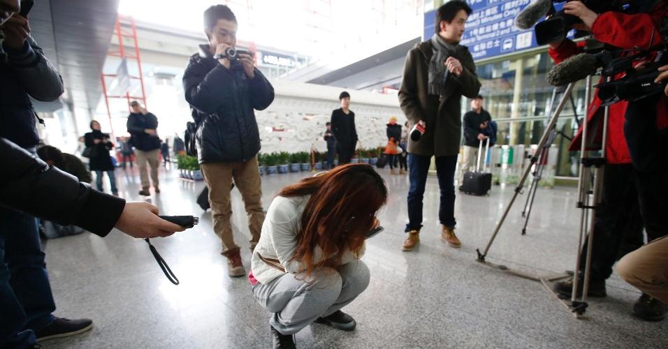 8.mar.2014 - Jornalista tenta entrevistar chinesa que chora enquanto espera por informações de passageiros do voo MH370, da Malaysia Airlines, no Aeroporto Internacional de Pequim