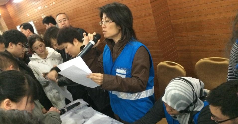 9.mar.2014 - Funcionário da Malaysia Airlines conversa com familiares dos passageiros do voo MH370, que desapareceu quando ia para a China. A empresa prometeu atualizar as informações a cada 15 minutos
