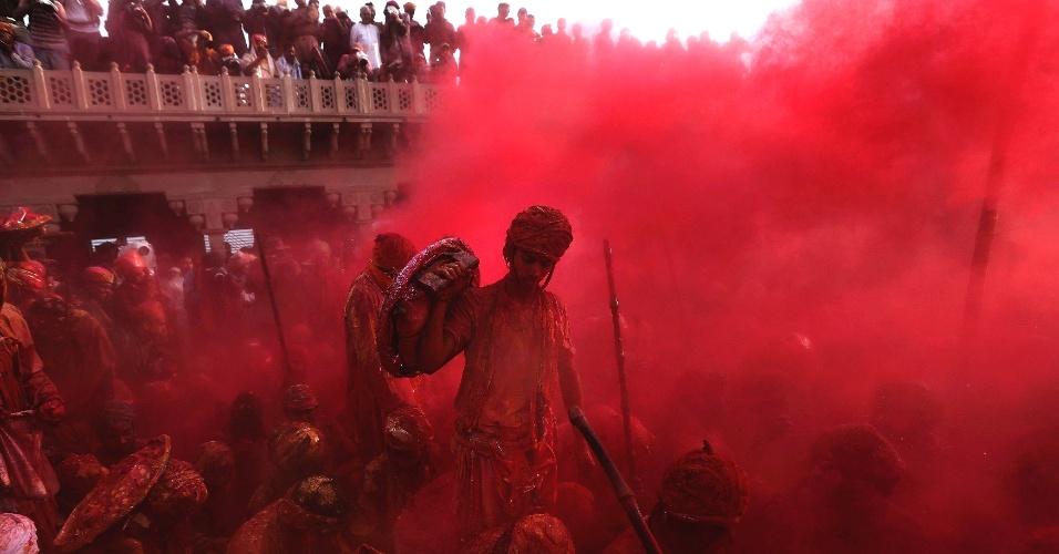 """10.mar.2014 - As pessoas jogam pó colorido durante a celebração do """"Lathmar Holi"""", na vila Nandgaon, no estado indiano de Uttar Pradesh, na Índia"""