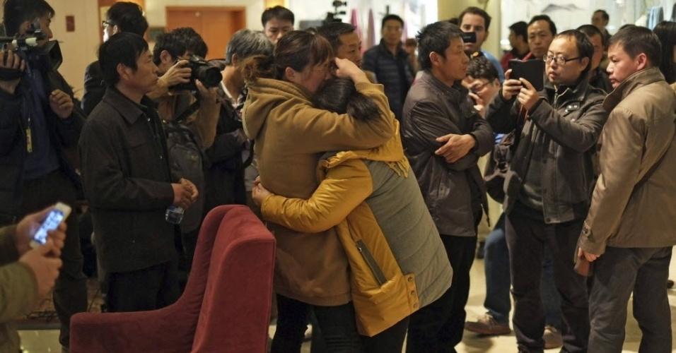 10.mar.2014 - Mulheres se abraçam enquanto aguardam notícias sobre o voo MH370, da Malaysia Airlines, que desapareceu no último sábado (8), em hotel de Pequim, na China