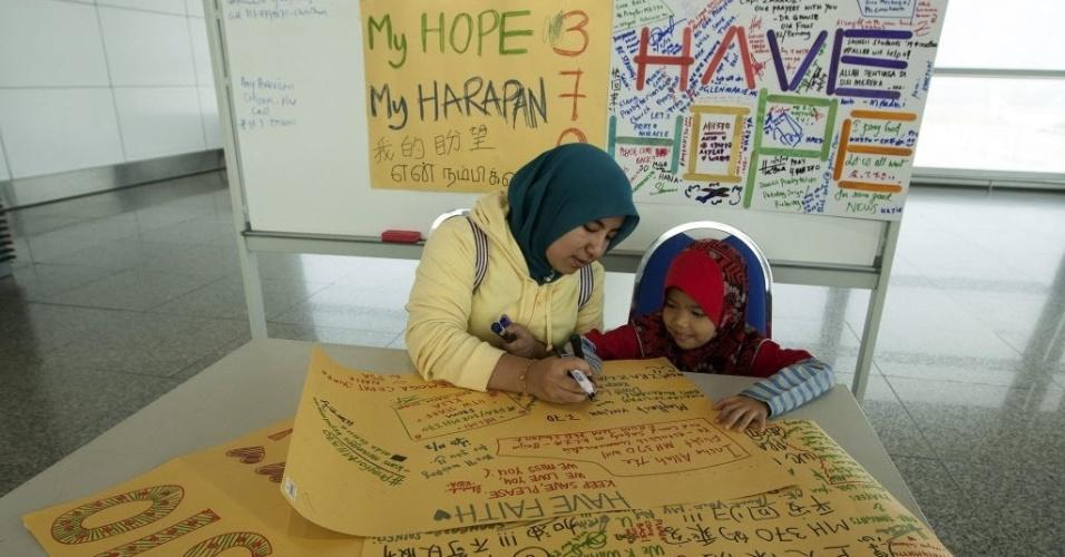 10.mar.2014 - No aeroporto internacional de Kuala Lumpur, na Malásia, mulher e criança escrevem em cartaz para mural dedicado aos passageiros do voo MH370, da Malaysia Airlines, desaparecido no último sábado (8).