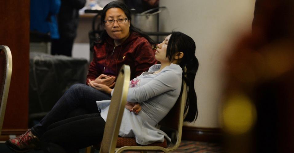 10.mar.2014 - Parentes de passageiros do voo MH370, da Malaysia Airlines, aguardam notícias do avião desaparecido no último sábado (8), em hotel em Pequim. O voo, que tinha como destino a capital chinesa, tinha 239 pessoas a bordo, entre passageiros e tripulantes