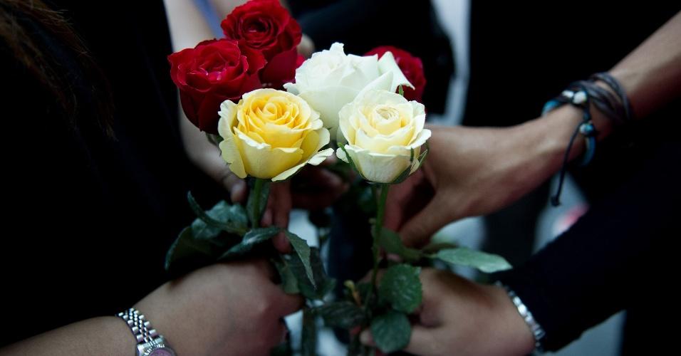 10.mar.2014 - Pessoas seguram rosas enquanto rezam em um hotel de Putrajaya, na Malásia, pelos passageiros do voo MH370, da Malaysia Airlines, que está desaparecido desde sábado (8)