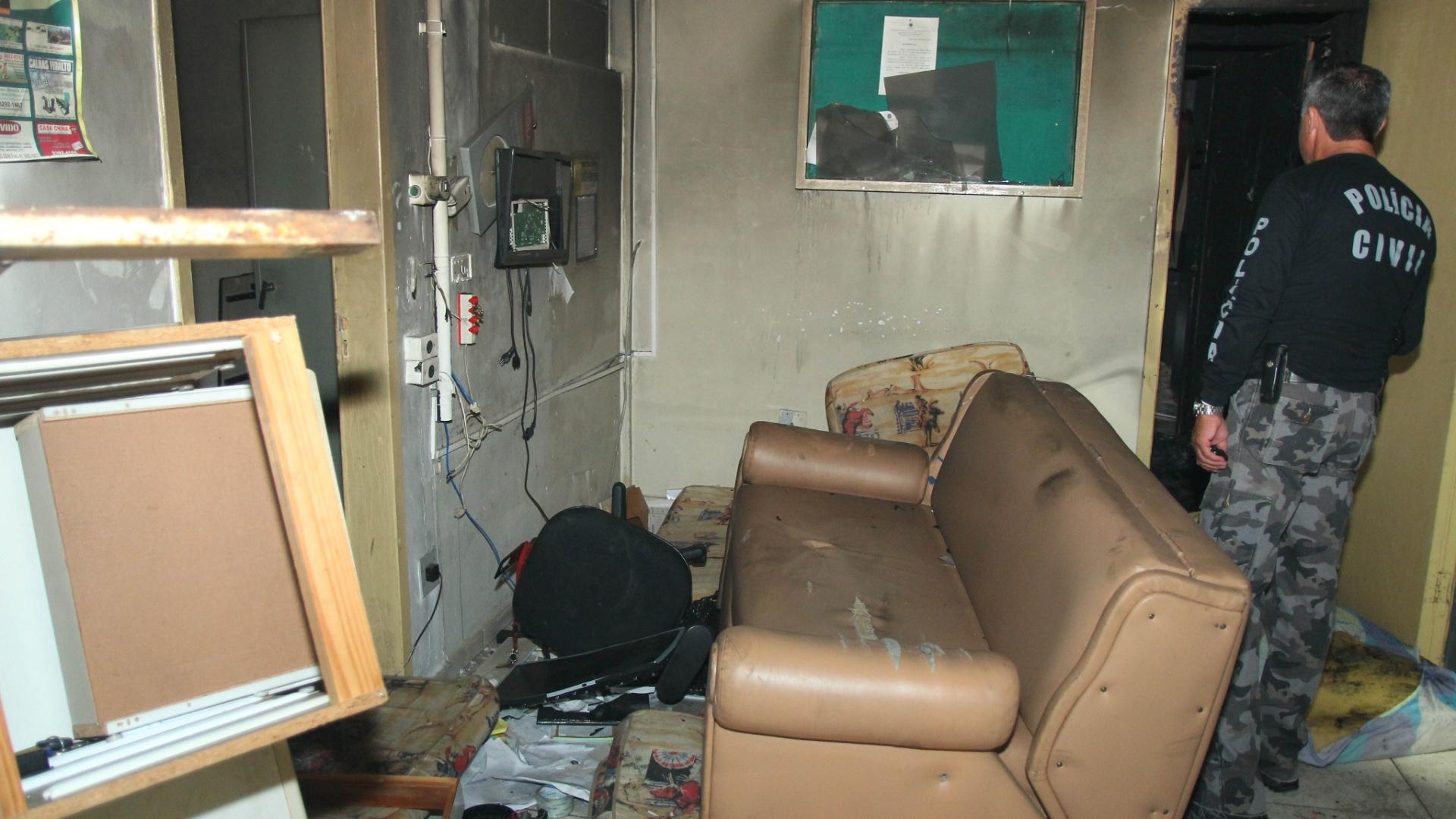 10.mar.2014 - Policial averigua ala destruída da delegacia de Campo Largo,