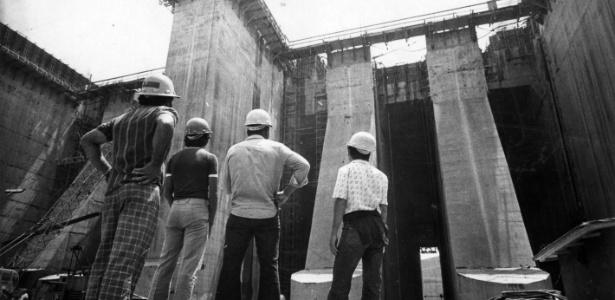 Trabalhadores observam obras da hidrelétrica Itaipu, cuja construção começou em 1974