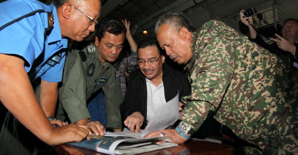 11.mar.2014 - Ministro dos Transportes da Malásia, Hishamuddin Hussein (terceiro da esquerda para a direita) discute o caminho para o chefe das Forças Armadas da Malásia, Mohd Zin Zulkifeli (à dir.), para sair com a equipe de resgate em busca dos desaparecidos do vôo MH370, da Malaysia Airlines, no estado de Selangor, na Malásia, nesta terça-feira (11)