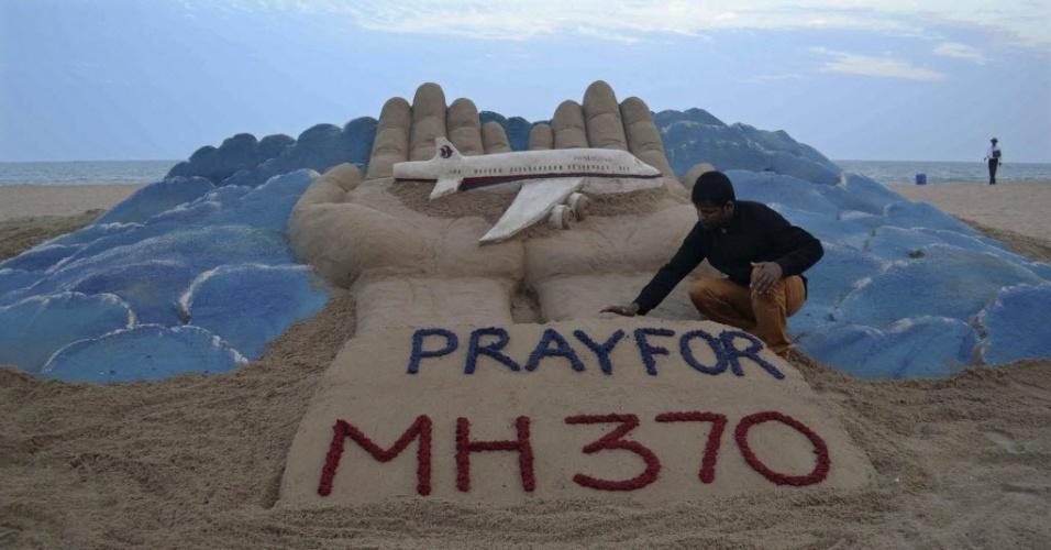 12.mar.2014 - Artista indiano de esculturas na areia, Sudarshan Pattnaik, trabalha em uma escultura pedindo que o povo reze pelos desaparecidos no avião da Malaysian Airlines, na praia dourada em Puri, no estado indiano oriental de Odisha, na Índia