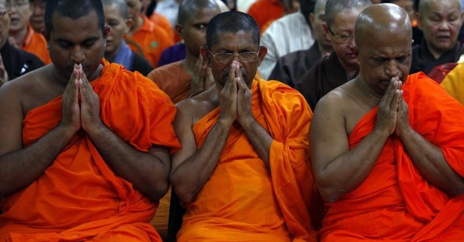 """12.mar.2014 - Monges budistas rezam durante orações de inter-religiosas chamada """"Esperança"""", pelos passageiros e tripulação do voo MH370 da Malaysia Airlines, na Malásia, que está desaparecido. O ato religioso acontece no templo budista em Kuala Lumpur, nesta quarta-feira (12). Satélites de observação da Terra pertencentes a 15 países estão procurando o avião a Malaysia Airlines desaparecido desde sábado (8) com 239 ocupantes, em virtude de um acordo internacional. Além disso, participam da missão de resgate do voo MH-370 aeronaves e embarcações de 20 países"""