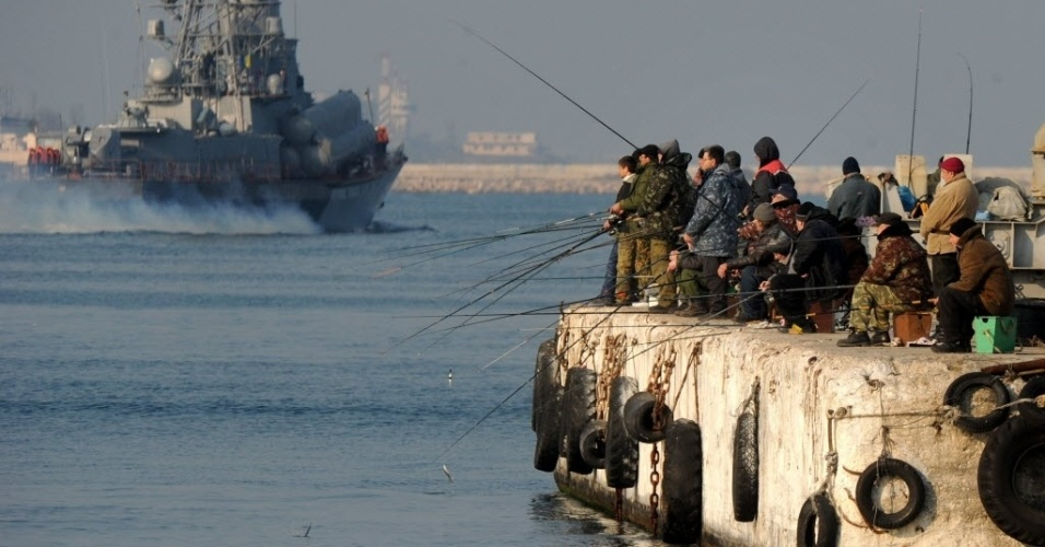 12.mar.2014 - Pessoas pescam em um cais próximo a uma embarcação naval russa em Sebastopol