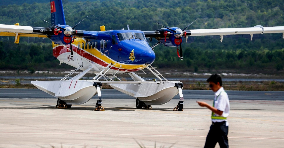 12.mar.2014 - Trabalhador vietnamita passa por aeronave de busca e salvamento no aeroporto de Phu Quoc, oeste do Vietnã, nesta quarta-feira (12). O país afirma que retomou as buscas aéreas pelo Boeing da Malaysian Airlines desaparecido há cinco dias
