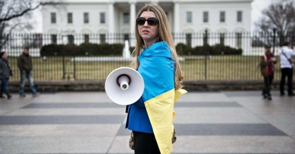 12.mar.2014 - Uma ativista se cobre com uma bandeira ucraniana do lado de for a da Casa Branca, durante uma manifestação contra o governo do presidente russo, Vladimir Putin, em Washington, durante o encontro entre o presidente dos EUA, Barack Obama, e o primeiro-ministro ucraniano, Arseniy Yatsenyuk