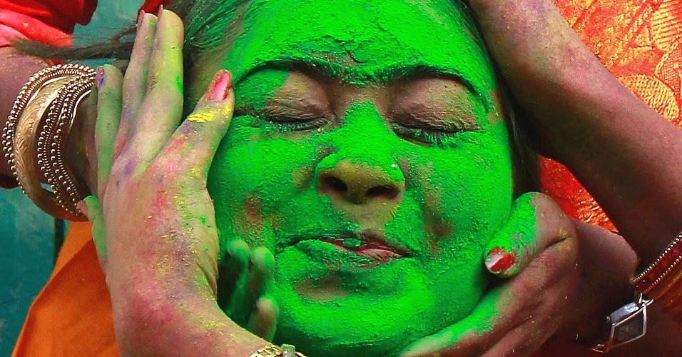 12.mar.2014 - Uma estudante da Universidade Rabindra Bharati reage quando seus colegas aplicam pó colorido em seu rosto durante as celebrações d festival Holi, também conhecido como o festival de cores em Calcutá, na Índia