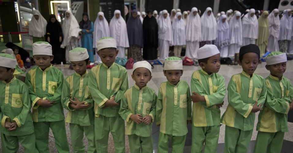 13.mar.2014 - Crianças muçulmanas fazem oração para os passageiros do avião da Malaysia Airlines desaparecido há seis dias