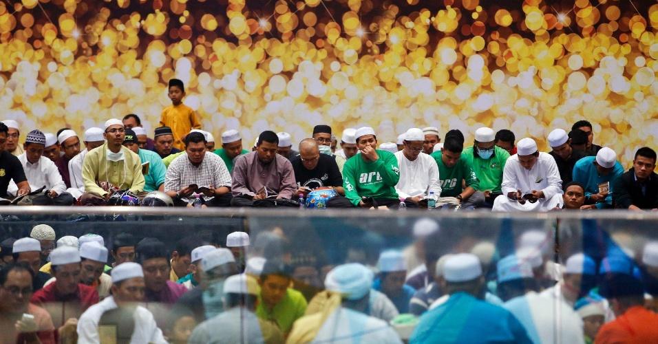 13.mar.2014 - Muçulmanos fazem uma oração especial para os passageiros do avião desaparecido Malaysia Airlines MH370 no salão de embarque do Aeroporto Internacional de Kuala Lumpur, na Malásia