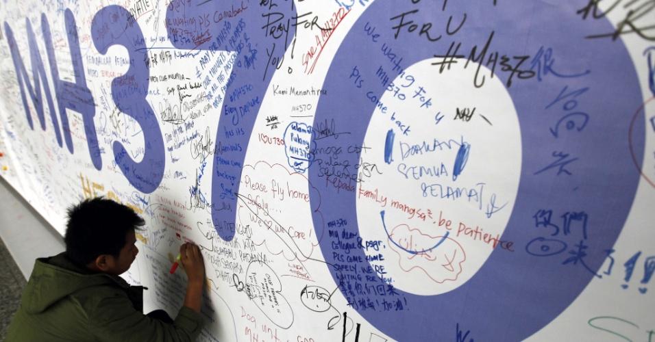 13.mar.2014 - Passageiro escreve mensagem em mural em homenagem aos desaparecido do voo Mh370, da Malaysian Airlines, no aeroporto internacional de Kuala Lumpur (Malásia). As autoridades da Malásia anunciaram que uma esquadrilha enviada para verificar o local onde o governo chinês afirmou na quarta-feira ter visto, via satélite, objetos flutuando