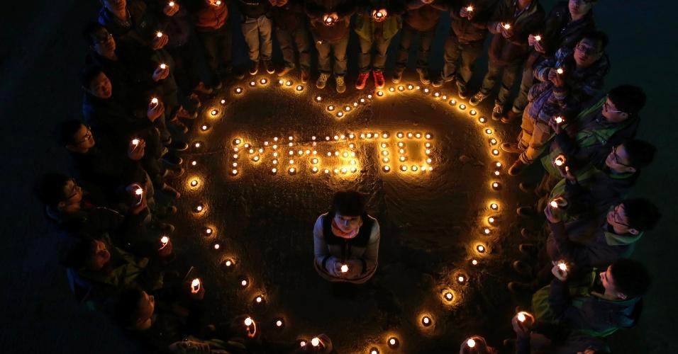 13.mar.2014 - Trabalhadores do setor da construção acendem velas em Wuhan, na China, durante oração pela 239 pessoas presentes no voo MH370. O avião desapareceu no sábado (8) após partir da capital da Malásia em direção a Pequim