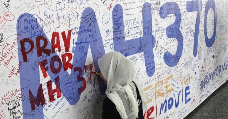 14.mar.2014 - Mulher escreve mensagem em mural dedicado aos passageiros do voo MH370 da Malaysia Airlines, no aeroporto internacional de Kuala Lumpur, na Malásia. Com 239 pessoas a bordo, o voo está desaparecido desde o último sábado (8)
