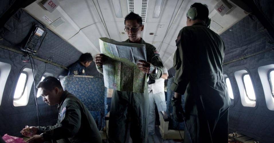 14.mar.2014 - Oficial da Força Aérea da Malásia estuda mapa a bordo de avião militar durante operação de busca do avião da Malaysia Airlines que está desaparecido desde o último sábado (8)