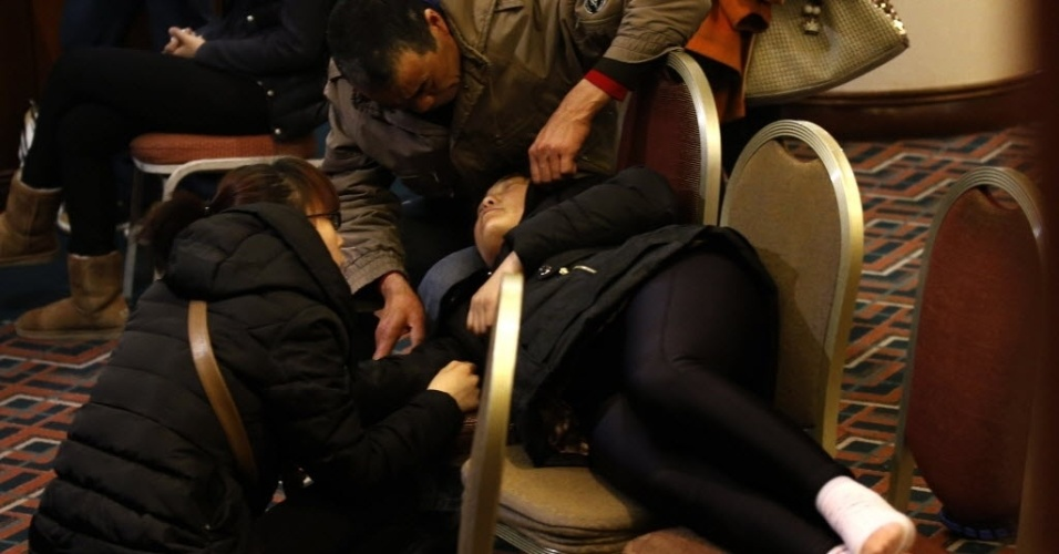 14.mar.2014 - Parente de passageiro do voo MH370 da Malaysia Airlines descansa em cadeiras em hotel de Pequim, na China, enquanto aguarda notícias do paradeiro do avião, que está desaparecido desde o último sábado (8)